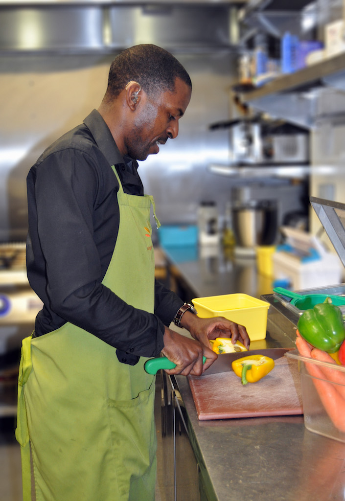 Wycliffe is cutting vegetables in the cafe's kitchen.